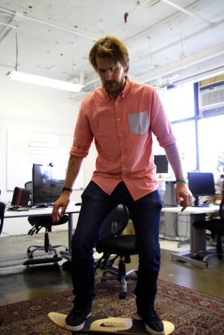 Sam demonstrates a balanced pose in a balanced workplace via Bengo board.